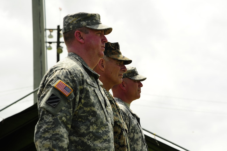 U. S. Army Col. Kirk C. Dorr, (left), U. S. Marine Gen. John F. Kelly, U. S. Southern Command commander, and U. S. Army Col. Thomas D. Boccardi watch as Joint Task Force-Bravo major support commands march in pass and review during a change of command ceremony at Soto Cano Air Base, Honduras, June 23, 2014.  Col. Dorr assumed command of Joint Task Force-Bravo from Col. Boccardi.  (Photo by Martin Chahin)