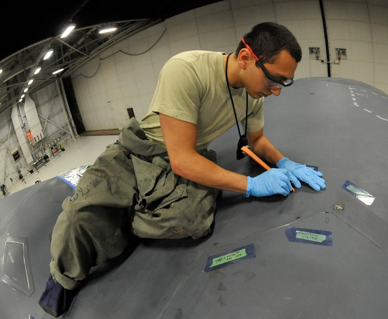 Senior Airman Alexander Ramirez, 509th MXS Low Observable aircraft structural maintainer, inspects thin tape in the B-2 Spirit's arrsi door at Whiteman Air Force Base, Mo., June 12, 2014. If the tape reaches a certain point of negligible damage, it must be removed and replaced. (U.S. Air Force photo by Airman 1st Class Keenan Berry/Released)