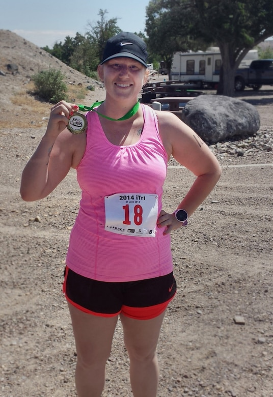 Gina Paige, 366th Force Support Squadron Marketing Department private organization monitor, poses for a photo with her medal after crossing the finish line of the fourth Annual iTri at Strike Dam, Idaho, June 21, 2014. The triathlon included a 300-meter swim, 12.4-mile bike ride and a 3.1-mile run starting and ending at CJ Strike Reservoir. (U.S. Air Force photo by Staff Sgt. Joshua Paige/Released)