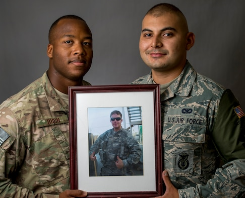 Deployed photo of U.S. Air Force Staff Sgt. Mark Bush and Senior Airman Esteban Salazar holding a photograph of their friend, Kevin Brunais. (U.S. Air Force photo by Staff Sgt. Jeremy Bowcock)