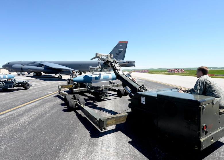 Airman 1st Class Dustin Lumpkin and Airman Michael Page, 5th Aircraft Maintenance Squadron weapons load crew members, transport a GBU-31 onto a B-52 Stratofortress at Ellsworth Air Force Base, S.D., June 9, 2014. It takes six weeks for weapons load crew members to become certified on controlling, maintaining and installing aircraft bombs. (U.S. Air Force photo by Senior Airman Anania Tekurio/Released)