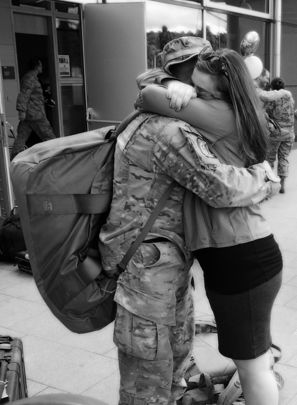 Senior Airman Chris Willis is greeted by his wife, Rena, after returning home from a six-month deployment to Afghanistan, May 15, 2013, Ramstein Air Base, Germany. (courtesy photo)