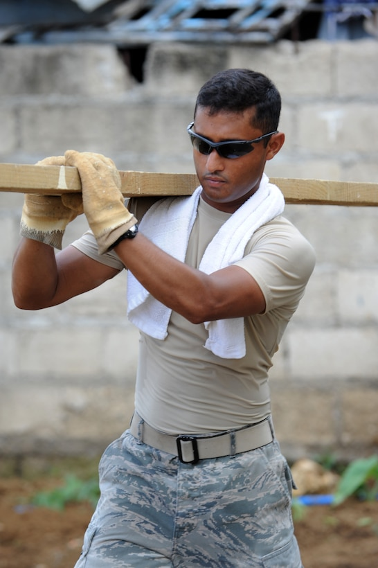 Senior Airman Ariful Haque carries a plank away from a construction site June 18, 2014, as cleanup begins at Buyong Elementary School in Barangay Maribago, Lapu-Lapu City, Philippines. Airmen from the 374th Civil Engineer Squadron, Yokota Air Base, Japan, spent 31 days building two classrooms and renovating utilities throughout the school as part of Operation Pacific Unity 14-6, a bilateral engineering program meant to strengthen ties with regional partners throughout the Asia-Pacific region. Haque is a utilities journeyman with the 374th CES. (U.S. Air Force photo/Staff Sgt. Amber E. N. Jacobs)