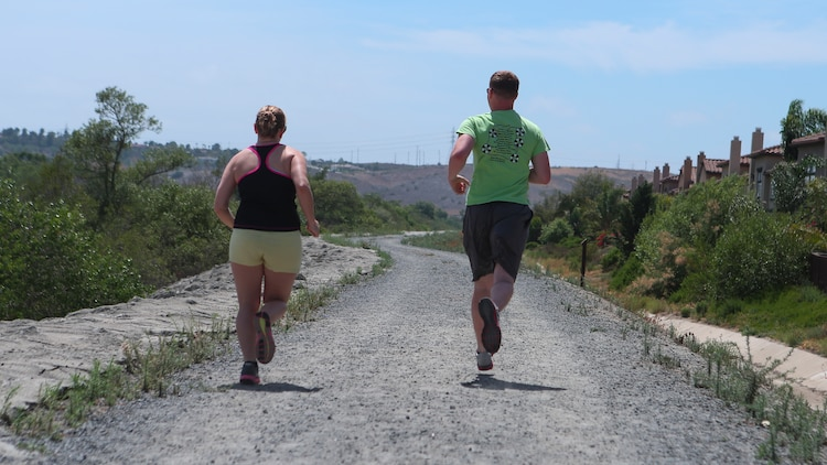Corporal Dalton Pridmore, intelligence analyst, 15th Marine Expeditionary Unit, runs with his wife, Jamie Pridmore, in Oceanside, Calif., June 20, 2014. Pridmore and his wife are from Moody, Alabama. (U.S. Marine Corps photo by Lance Cpl. Anna Albrecht/Released)