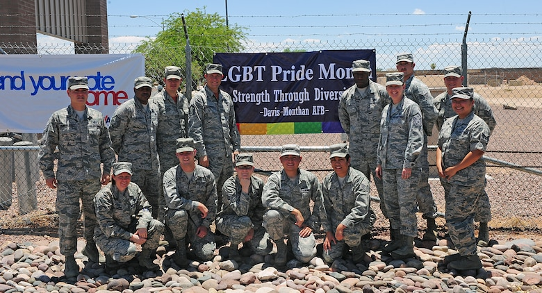 Members of the LGBT Pride Observance Month Committee pose for a photo in front of their banner at Davis-Monthan Air Force Base, Ariz., June 20, 2014. In an effort to educate the base populous, the LGBT Pride Observance Committee is hosting an Informational Fair on the 27th of June at the Mirage Club from 1100 to 1300. (U.S. Air Force photo by Senior Airman Camilla Elizeu/Released)