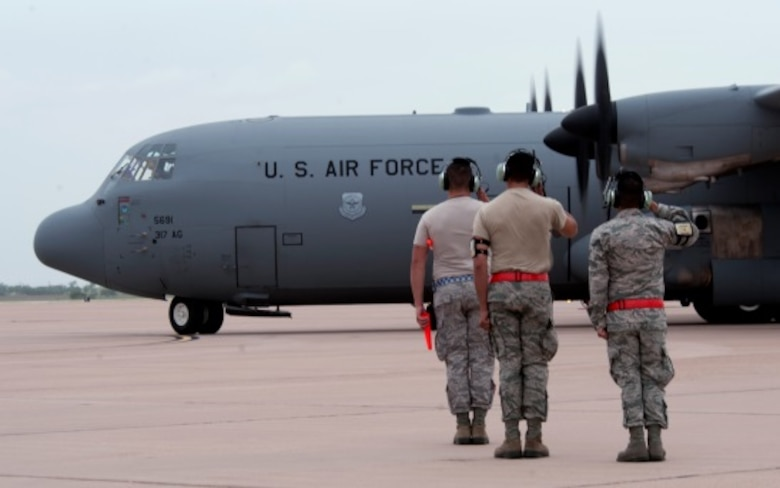 U. S. Air Force Airmen from the 317th Aircraft Maintenance Squadron salute a C-130J Super Hercules as it taxis towards the runway June 21, 2014, at Dyess Air Force Base, Texas. Aircrews at Dyess launched 21 C-130s from multiple units to fly in a large formation. (U.S. Air Force photo by Senior Airman Peter Thompson/Released)