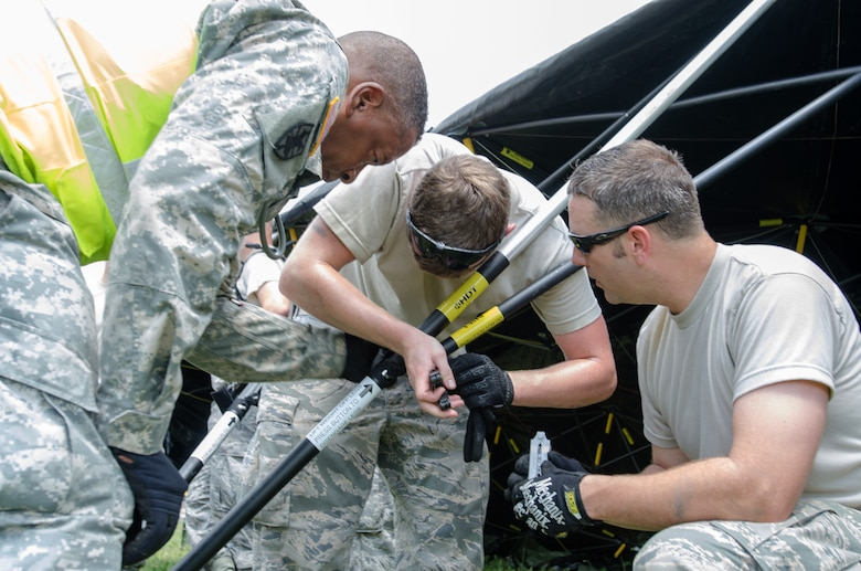 Personnel from the Kentucky Air National Guard's 123rd Contingency Response Group and the U.S. Army's 688th Rapid Port Opening Element work together to erect a Base X tent at Fort Campbell, Ky., on June 17, 2014, while participating in at Capstone '14, a homeland earthquake-response exercise. The 123rd CRG joined with the 688th RPOE to operate a Joint Task Force-Port Opening from June 16 to 19, 2014. (U.S. Air National Guard photo by Master Sgt. Phil Speck)