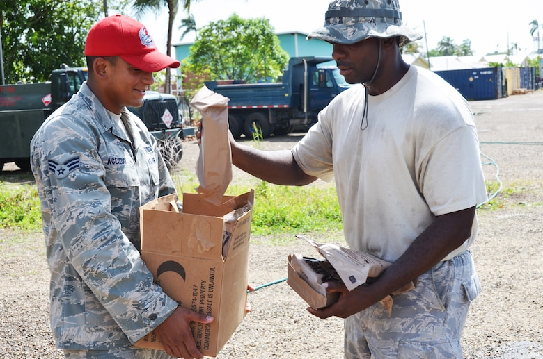 Senior Airman Mario Acevedo (left), a New Horizons services journeyman deployed from the 820th RED HORSE Squadron, Nellis Air Force Base, Nevada, issues MREs to Staff Sgt. Smette Pompfilius, New Horizons vehicle maintenance, June 24, 2014, in Ladyville, Belize.
