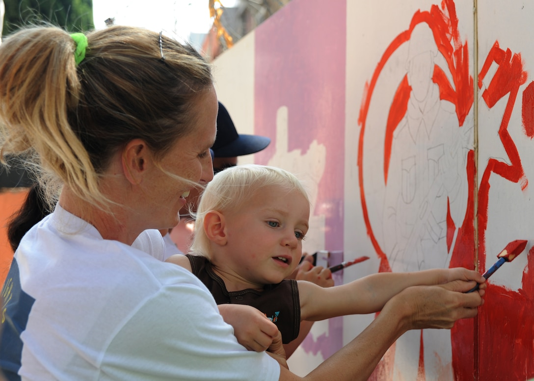 Linne Gherdovich and son Hudson, paint a mural of a Turkish soldier at the Kazim Karabekir School for Autism, June 9, 2014, Adana, Turkey. Gherdovich is a coordinator with the organization Love Impact Give Help Teach Serve, or LIGHTS located at Incirlik Air Base, Turkey. The group of active duty members, civilians and dependents of all ages focuses on helping the community with simple art projects at special needs schools around Adana. (U.S. Air Force photo by Staff Sgt. Veronica Pierce/Released)