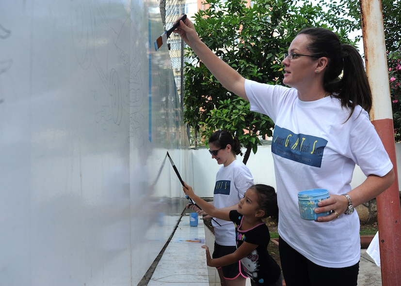 Irina Rodriguez and daughter Isabella, paint a mural at the Kazim Karabekir School for Autism, June 9, 2014, Adana, Turkey. Rodriquez is part of the volunteer organization located at Incirlik Air Base, Turkey, called Love Impact Give Help Teach Serve, or LIGHTS. The group is made up of volunteers who are active duty members, civilians and dependents of all ages. (U.S. Air Force photo by Staff Sgt. Veronica Pierce/Released)
