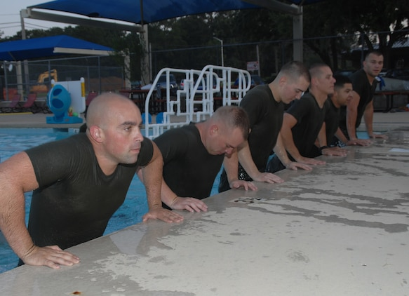 Marines conduct poolside pushups during the Aquatics Maximum Power-Intense Training Program at the Base Pool aboard Marine Corps Logistics Base Albany, recently. AMP-IT, an aquatic version of the High Intensity Tactical Training Program, is a high-intensity, high-cardio, but low-impact workout that works the chest, back, legs, shoulders, biceps and triceps.