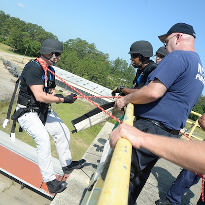 Officer Bruce Owens, a member of the Special Reaction Team, Marine Corps Police Department (left) begins his rappel, June 6, under the watchful eye of team members and Marine Corps Logistics Base Albany Fire Department personnel.