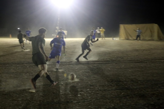 "Corporal Ben McCabe, fire team leader, ""Suicide"" Charley Company, 1st Battalion, 7th Marine Regiment, and a native of North Canton, Ohio, prepares to pass the ball to a teammate during the championship game in the Dwyer World Cup aboard Camp Dwyer, Helmand province, Afghanistan, June 22, 2014. A total of four teams participated in the tournament to include Team America, Afghanistan, Jordan and the World Team (consisting of contractors on the camp). The Marines ultimately defeated the World Team during the final game and were the champions of the tournament.  (U.S. Marine Corps photo by Cpl. Joseph Scanlan / released)"