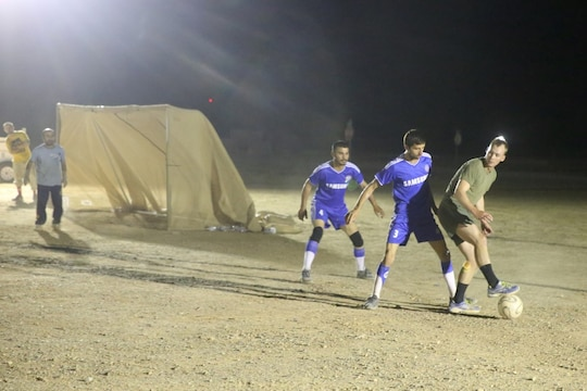 "Corporal Kodie Artmayer, rifleman, ""Suicide"" Charley Company, 1st Battalion, 7th Marine Regiment, and a native of Harrison, Ohio, attempts to maneuver around a defender during the championship game in the Dwyer World Cup aboard Camp Dwyer, Helmand province, Afghanistan, June 22, 2014. A total of four teams participated in the tournament to include Team America, Afghanistan, Jordan and the World Team (consisting of contractors on the camp). The Marines ultimately defeated the World Team during the final game and were the champions of the tournament. (U.S. Marine Corps photo by Cpl. Joseph Scanlan / released)"