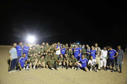 "Marines with ""Suicide"" Charley Company, 1st Battalion, 7th Marine Regiment, pose for a photo with their opponents after winning the championship game in the Dwyer World Cup aboard Camp Dwyer, Helmand province, Afghanistan, June 22, 2014. A total of four teams participated in the tournament to include Team America, Afghanistan, Jordan and the World Team (consisting of contractors on the camp). The Marines ultimately defeated the World Team during the final game and were the champions of the tournament. (U.S. Marine Corps photo by Cpl. Joseph Scanlan / released)"