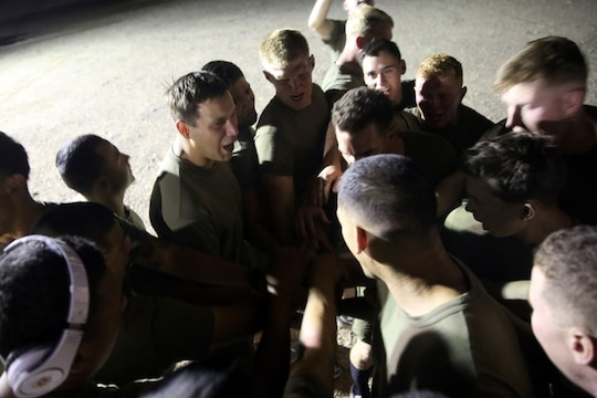"Marines with ""Suicide"" Charley Company, 1st Battalion, 7th Marine Regiment, gather in a huddle before their first game in the Dwyer World Cup aboard Camp Dwyer, Helmand province,  Afghanistan, June 21, 2014. A total of four teams participated in the tournament to include Team America, Afghanistan, Jordan and the World Team (consisting of contractors on the camp). The Marines ultimately defeated the World Team during the final game and were the champions of the tournament. (U.S. Marine Corps photo by Cpl. Joseph Scanlan / released)"