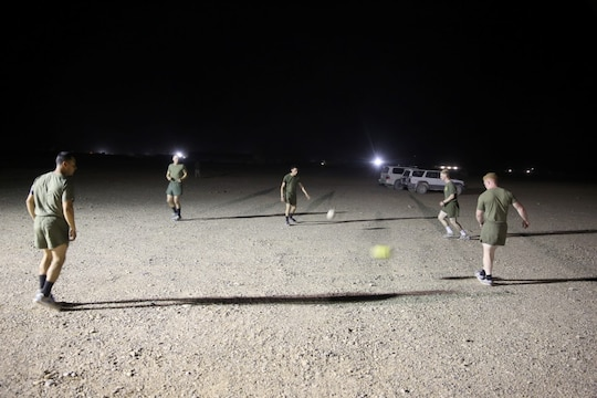 "Marines with ""Suicide"" Charley Company, 1st Battalion, 7th Marine Regiment, conduct passing drills prior to their first match in the Dwyer World Cup aboard Camp Dwyer, Helmand province, Afghanistan, June 21, 2014. A total of four teams participated in the tournament to include Team America, Afghanistan, Jordan and the World Team (consisting of contractors on the camp). The Marines ultimately defeated the World Team during the final game and were the champions of the tournament. (U.S. Marine Corps photo by Cpl. Joseph Scanlan / released)"