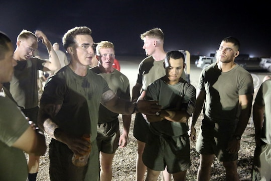 "Corporal Ben McCabe, left, fire team leader, ""Suicide"" Charley Company, 1st Battalion, 7th Marine Regiment, and a native of North Canton, Ohio, speaks to his teammates in a huddle during their first match in the Dwyer World Cup aboard Camp Dwyer, Helmand province, Afghanistan, June 21, 2014. A total of four teams participated in the tournament to include Team America, Afghanistan, Jordan and the World Team (consisting of contractors on the camp). The Marines ultimately defeated the World Team during the final game and were the champions of the tournament. (U.S. Marine Corps photo by Cpl. Joseph Scanlan / released)"