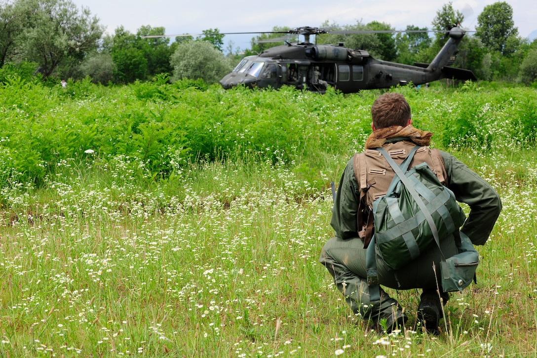 Capt. William Flynt  waits for a UH-60 Black Hawk helicopter during a combat search and rescue training mission, June 24, 2014, at Cellina Meduna training ground near Maniago, Italy. Pilots are taught necessary survival skills to evade capture and get recovered successfully to include: movement, camouflage and signaling techniques. Flynt is a F-16 Fighting Falcon pilot with the 555th Fighter Squadron. (U.S. Air Force photo/Airman 1st Class Ryan Conroy)