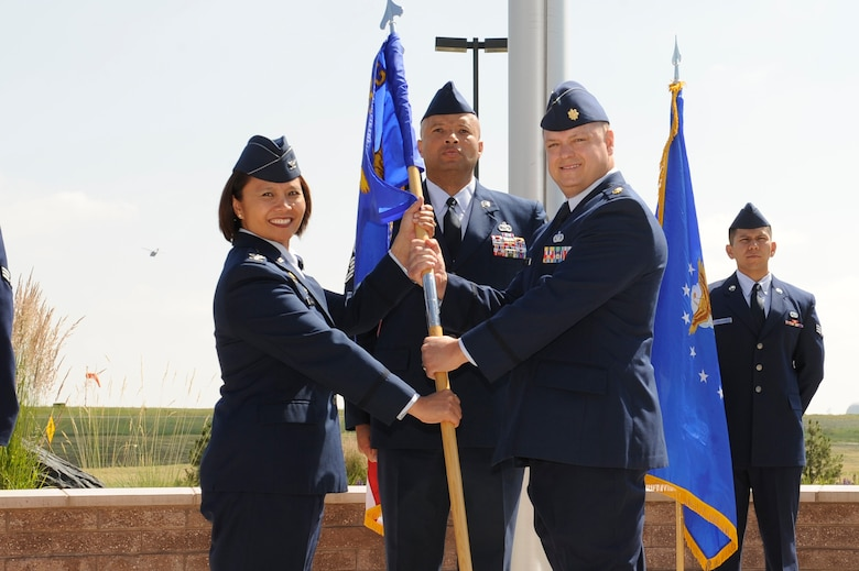 Maj. Gene Smith, 460th Contracting Flight commander receives the 460th Mission Support Group guidon from Col. Rose Jourdan, 460th MSG commander, during the 460th CONF Change of Command Ceremony June 24, 2014, at the 460th Space Wing headquarters building on Buckley Air Force Base, Colo. The event signals Smith's assumption of command from Maj. Jeremy Morrill. (U.S. Air Force photo by Airman 1st Class Samantha Saulsbury/Released)