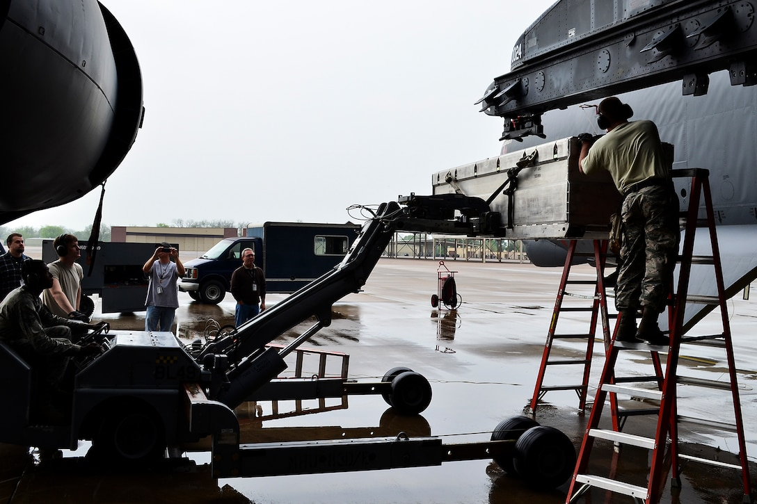 A casket containing the AN/ASQ-236 Radar Pod is lifted to a mounting station on a 93rd Bomb Squadron B-52H Stratofortress, April 14, 2014, Barksdale Air Force Base, Louisiana. This marks the first test of the pod on a B-52, which will give the aircraft the ability to precisely geo-locate points of interest and conduct surveillance activities day or night, in adverse weather conditions. (U.S. Air Force photo by Master Sgt. John Paxton/Released)