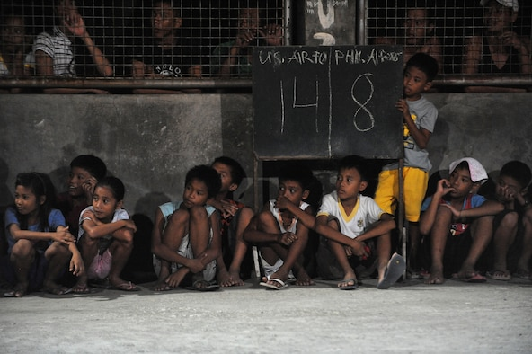 Children observe a basketball game between U.S. Airmen and Philippine airmen June 19, 2014, at Buyong Elementary School in Barangay Maribago, Lapu-Lapu City, Philippines. The service members were participating in Operation Pacific Unity 14-6, a 31-day bilateral project that renovated utilities and constructed classrooms for a school. The Airmen are assigned to the 374th Civil Engineer Squadron. (U.S. Air Force photo/Staff Sgt. Amber E. N. Jacobs)