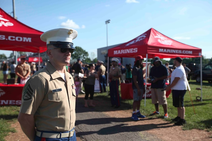 BRIDGEWATER, N.J. — Staff Sgt. Richard Ison, a canvassing recruiter with Recruiting Station New Jersey stands by the Marine Corps booths greeting families as they head towards their seats at the 2nd Annual Basilone Bowl at John Basilone Memorial Field, June 26.  The Basilone Bowl is a football game held to honor one of the Marine Corps greatest heroes, Gunnery Sgt. John Basilone, a recipient of the Medal of Honor and the Navy Cross. (U.S. Marine Corps photo by Lance Cpl. Brandon Thomas)