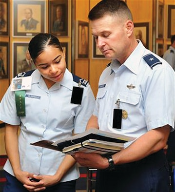 Then-Cadet 3rd Class Kayla Vidosola and then-Brig. Gen. Gregory Lengyel, the commandant of cadets, read a Falcon Heritage Forum schedule in Exemplar Hall in September 2012.