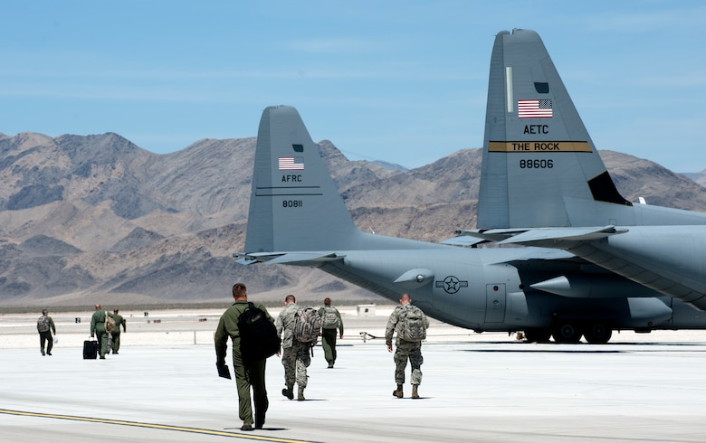 Aircrews of C-130H Hercules and C-130J Super Hercules step to their planes as they prepare to depart Creech Air Force Base, Nev., June 22, 2014.  Twelve C-130H and C-130J model aircraft participated in Joint Forcible Entry, an exercise designed to enhance service cohesiveness between the U.S. Army and Air Force. Both services work together to properly execute large scale heavy equipment and troop movement. (U.S. Air Force photo by Senior Master Sgt. Cecilio Ricardo/Released)