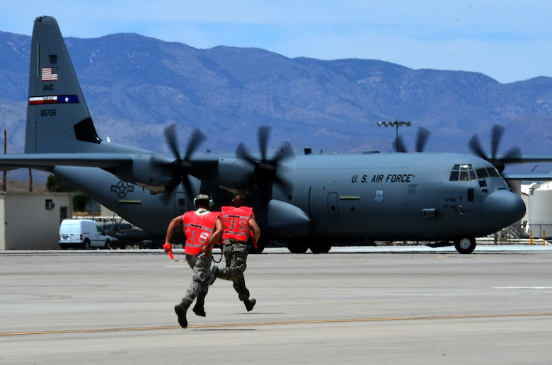 Airmen from the 818th Contingency Response Group, McGuire Air Force Base, N.J., run toward a C-130J Super Hercules from Dyess AFB, Texas, after it lands on the runway at Creech AFB, Nev., June 21, 2014. The 818th CRG Airmen and the aircraft participated in Joint Forcible Entry, an exercise designed to enhance service cohesiveness between the U.S. Army and Air Force. Both services work together to properly execute large scale heavy equipment and troop movement. (U.S. Air Force photo by Tech. Sgt. Nadine Barclay/Released)