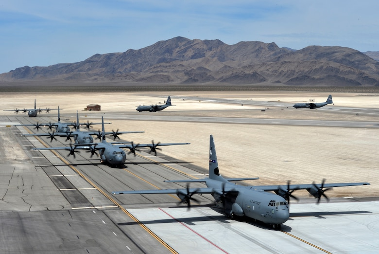 Seven C-130J Super Hercules aircraft taxi after landing at Creech Air Force Base, Nev., as part of Joint Forcible Entry exercise June 21, 2014. The aircraft were used to help Airmen and Soldiers from Nellis Air Force Base, Nev., and visiting units enhance service cohesiveness while allowing the opportunity to properly execute large scale heavy equipment and troop movement. (U.S. Air Force photo by 1st Lt. Stephani Schafer/Released)