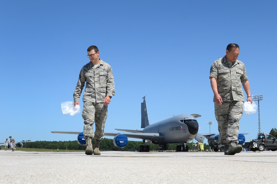 PEASE AIR NATIONAL GUARD BASE, N.H. – Senior Airman Aaron Loring and Tech. Sgt. Chui Chung, both of the 157th Comptroller Squadron, participate in a foreign object debris walk, or FOD walk, on the flightline here June 27. Airmen of the 157th Air Refueling Wing participated in the event that collected more than 40 pounds of debris. Among the items collected were bolts, safety wire, vehicle parts and more. (N.H. Air National Guard photo by Tech. Sgt. Mark Wyatt)