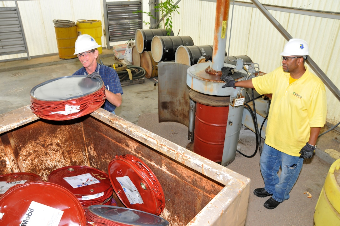 Personnel at AEDC's Recycling Facility crush empty steel drums that have been collected from various areas on base. After being crushed down to approximately 6-inches in height, the drums are then placed in a bin to be recycled. Pictured are Doug Richards and Charles Wilkerson with the AEDC Services Office. (Photo by Rick Goodfriend)