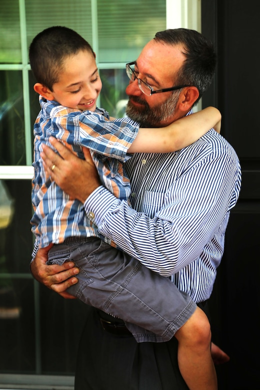 """Andrew Starr II, 7, and his father, retired Col. Andrew Starr, celebrate after the boy received the title, """"honorary Marine,"""" at his home in Springfield, Va., on June 30, 2014. Andrew, having suffered with Neurofibromatosis Type 1 since a baby, celebrated with family and friends."""