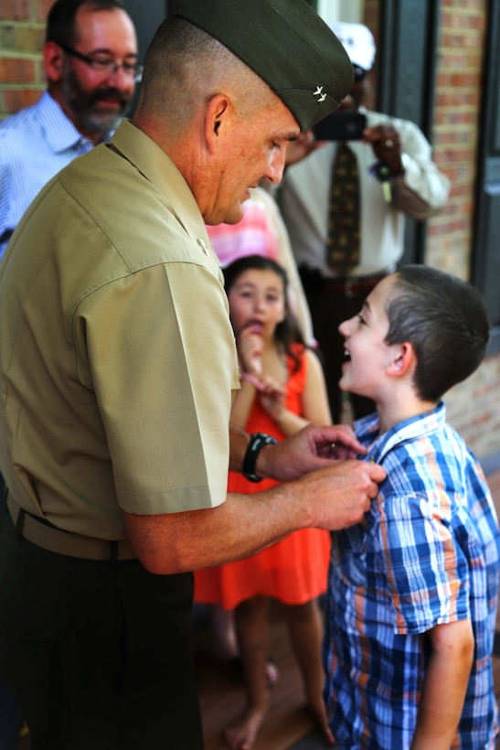 """Maj. Gen. Frederick Padilla, director of operations for Plans, Policies and Operations, Headquarters Marine Corps, pins an eagle, globe and anchor pin on Andrew Starr's lapel during a ceremony awarding Starr the title """"honorary Marine."""" Seven-year-old Andrew is one of less than 100 people to ever receive the title since its conception in 1992."""