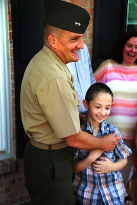 "Maj. Gen. Frederick Padilla, director of operations for Plans, Policies and Operations, Headquarters Marine Corps, celebrates with Andrew Starr after a ceremony awarding Starr the title ""honorary Marine."" Seven-year-old Andrew, having been diagnosed with Neurofibromatosis Type 1, is only the second person to receive the title in 2014."