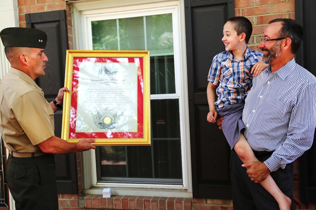 Maj. Gen. Frederick Padilla, director of operations for Plans, Policies and Operations, Headquarters Marine Corps, presents Andrew Starr II with an honorary Marine certificate on June 30, 2014, at Starr's home in Springfield, Va. Andrew's father, retired Marine Col. Andrew Starr, watched as his son, the second recipient of the title this year, received the award.