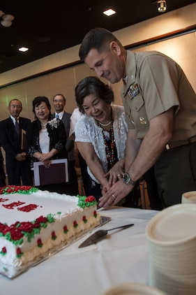 Col. Robert Boucher, Marine Corps Air Station Iwakuni, Japan, commanding officer, and Missie Hamano, a retiring Japanese employee, cut a cake during a retirement ceremony for Master Labor Contract and Independent Hire Agreement employees that took place in the Landing Zone inside Club Iwakuni Aboard Marine Corps Air Station Iwakuni, Japan, June 25, 2014.