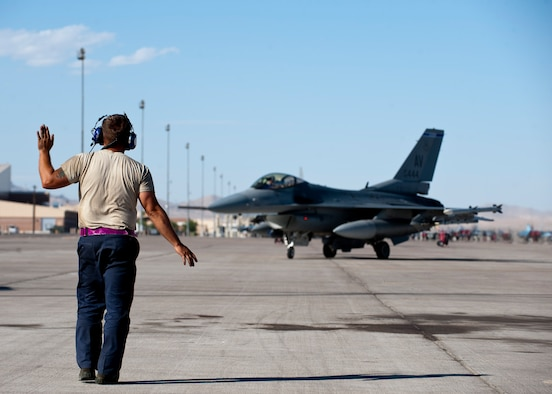 U.S. Air Force Senior Airman Joseph Archuleta, a crew chief assigned to the 510th Aircraft Maintenance Squadron, Aviano Air Base, Italy, directs an F-16 Fighting Falcon from the 31st Fighter Wing, Aviano AB, during Green Flag West 14-8, June 26, 2014, at Nellis Air Force Base, Nev. Green Flag West provides air and ground crews the opportunity to hone their skills and gain efficiency for future real-world operations. (U.S. Air Force photo by Airman 1st Class Thomas Spangler)