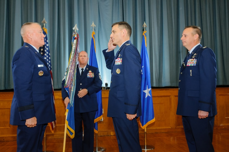 Col. David Snoddy (center) salutes Maj. Gen. J. Kevin McLaughlin (left) during the 67th Cyberspace Wing change of command ceremony June 20 at Joint Base San Antonio-Lackland.  Snoddy assumed command  from Col. William Poirier, who had led the wing since 2012.  (U.S. Air Force photo/William Belcher)