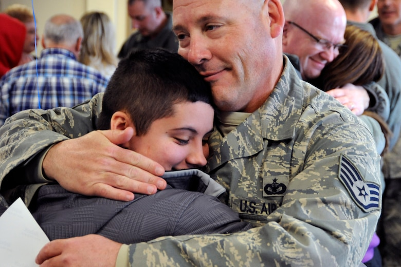 SSgt Andrew White, 127th Security Forces Squadron, receives hugs from his family on March 2, 2014, at Selfridge Air National Guard Base, Mich., after being deployed for 6 months to southwest Asia. (U.S. Air National Guard photo by John S. Swanson / Released)