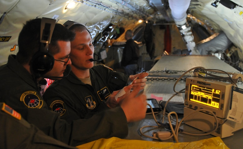 U.S. Air Force Tech. Sgt. Daniel Nelson, left, and Senior Airman John Leithead, right, both assigned to the 775th Expeditionary Aeromedical Evacuation Flight, Joint Base Andrews, Md., review a wounded service member's vital signs while monitoring the patient' s heart rate and oxygen levels during the aeromedical transport of patients from Joint Base Andrews to Marine Corps Air Station Miramar, San Diego, aboard a KC-135 Stratotanker assigned to the 128th Air Refueling Wing, Milwaukee, Jan. 13, 2014. The two Airmen are part of the five-person EAEF team aboard the KC-135 in support of a total force integration aeromedical evacuation mission. (U.S. Air National Guard photo by Staff Sgt. Jeremy Wilson/Released)