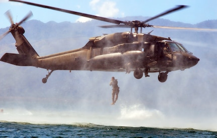 A member of Joint Task Force-Bravo jumps from a UH-60 Blackhawk helicopter during helocast training at Lake Yojoa, Honduras, Feb. 25, 2014. Several members of the Task Force spent the day training on helocasting, caving ladder, and overwater hoist operations. (U.S. Air Force photo by Capt. Zach Anderson)