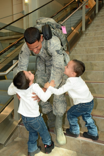 Staff Sgt. Nathan Ortiz, fire team member for the Wis. Air National Guard's 115th Fighter Wing Security Forces Squadron returns to Dane County Regional Airport in Madison, Wis. March 2, where he is reunited with his sons Jowell and Jariel for the first time in over six months. Twenty six members of the Wing's Security Forces Squadron deployed in support of Operation Enduring Freedom/Combined Joint Task Force-Horn of Africa and secured 3,500 personnel and $7.2 billion worth of assets within their area of responsibility. (Air National Guard photo by Master Sgt. Paul Gorman)