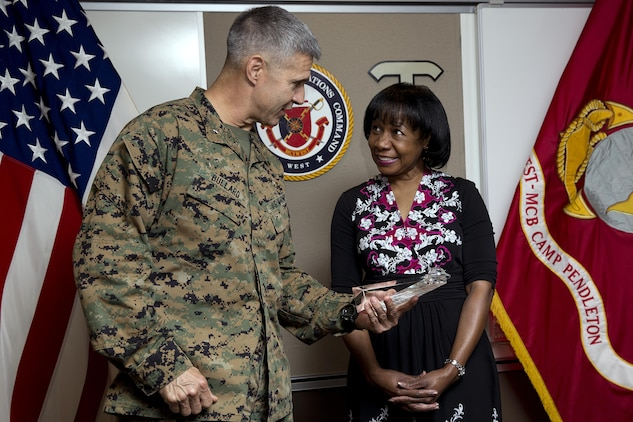 Brig. Gen. John W. Bullard presents Henrietta Pearman with the Outstanding Middle Housing Manager of the year award March 4.