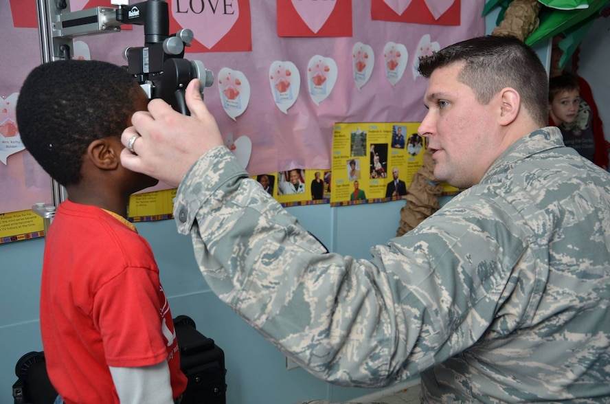 New Jersey Air National Guardsman Maj. Jason Winterbottom examines a child's eyes during a Cajun Care 2014 community outreach effort at the Lighthouse Christian Academy in Abbeville, La., Feb. 28. Winterbottom is participating in Cajun Care 2014, one of the Department of Defense's largest community outreach efforts in the Delta Region, is an Innovative Readiness Training mission designed to provide U.S. military medical professionals invaluable training as well as provide health care options to a medically underserved community.  (U.S. Navy photo by Pett Officer 1st Class Bruce Cummins)