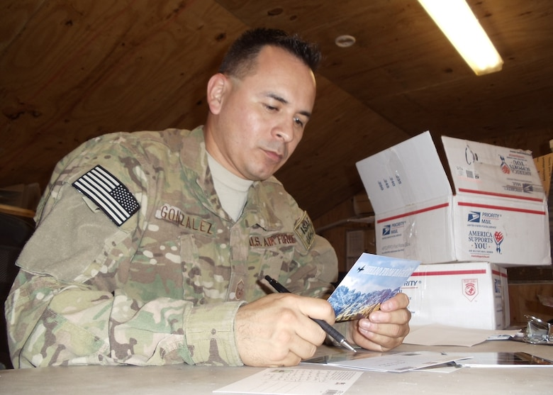 Then MSgt Jose M. Gonzalez prepares a postcard to a Tucson, AZ Veterans of Foreign Wars chapter in appreciation to recent care packages his unit received.
