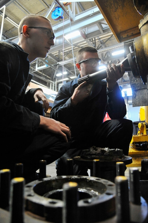 U.S. Air Force Air Force Airman 1st Class Cody Smith, 509th Logistics Readiness Squadron vehicle maintenance journeyman, left, and Staff Sgt. Kyle Bemis, 509th Logistics Readiness Squadron vehicle maintenance craftsman, remove broken axle shot at Whiteman Air Force Base, Mo., Feb. 21, 2014. The axle shot works with the differential to help the vehicle to move. (U.S. Air Force photo by Airman 1st Class Keenan Berry/Released)
