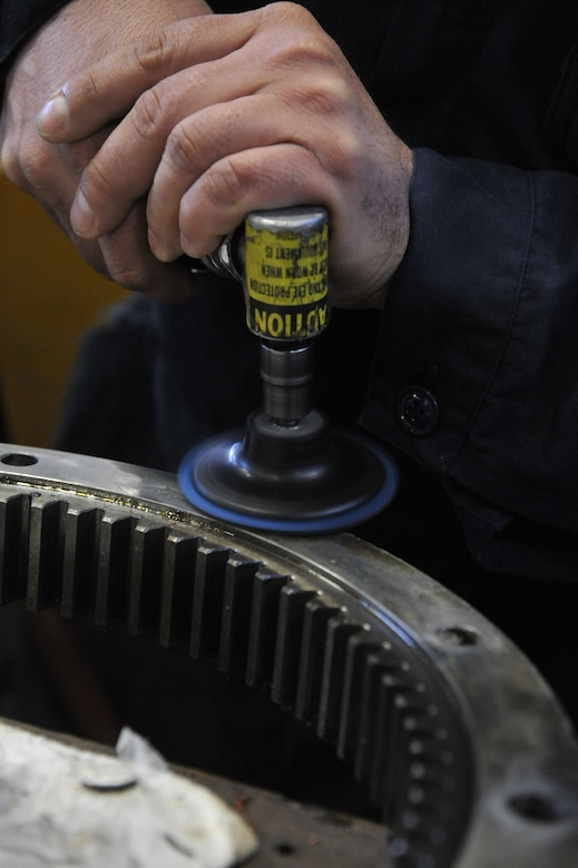 U.S. Air Force Tech Sgt. Dan Early, 509th Logistics Readiness Squadron NCO in charge of high bay, uses an abrasive wheel to clean a sun gear at Whiteman Air Force Base, Mo., Feb. 21, 2014. This tool is used to clean the surface and ensure the seals are flush. (U.S. Air Force photo by Airman 1st Class Keenan Berry/Released)