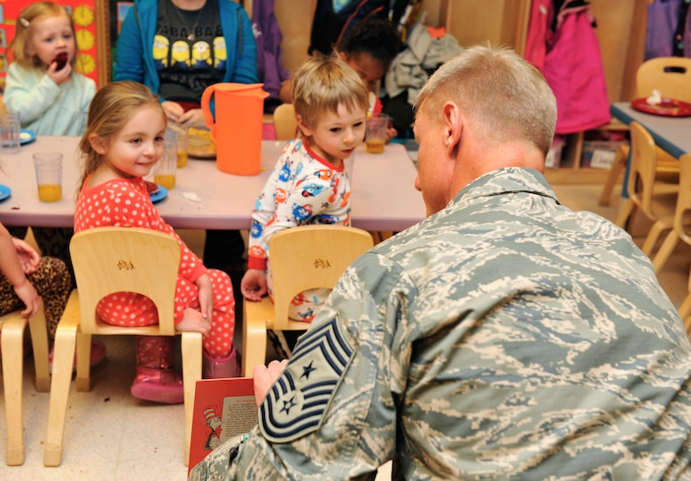 """Chief Master Sgt. Craig S. Hall, 460th Space Wing command chief, reads """"Green Eggs and Ham"""" to a preschool class Feb. 28, 2014, at the A-Basin Child Development Center on Buckley Air Force Base, Colo. Hall read to the children during their snack time to celebrate Dr. Seuss's birthday. (U.S. Air Force photo by Airman 1st Class Samantha Saulsbury/Released)"""